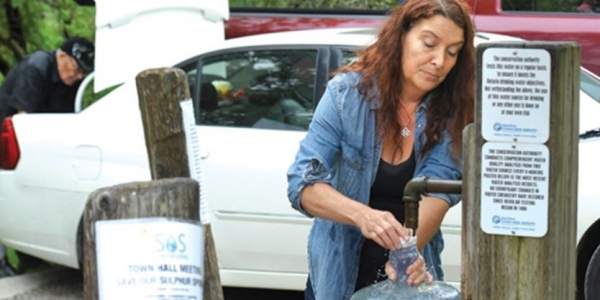 Joanne Turnell of Save Our Spring fills up a water jug at the Ancaster well. – Hamilton Spectator file photo